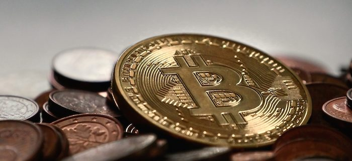 Picture of a bit coin on top os a pile of fiat currency coins