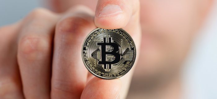 Close up picture of a bitcoin held in someone's fingers